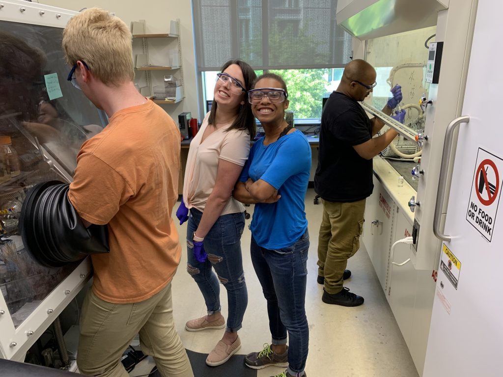 Research students are posing with big smiles in the lab.