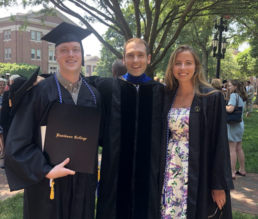 Nick Kennedy ('19) and Jennie Goodell ('19) standing with Mitch on the lawn after graduation.