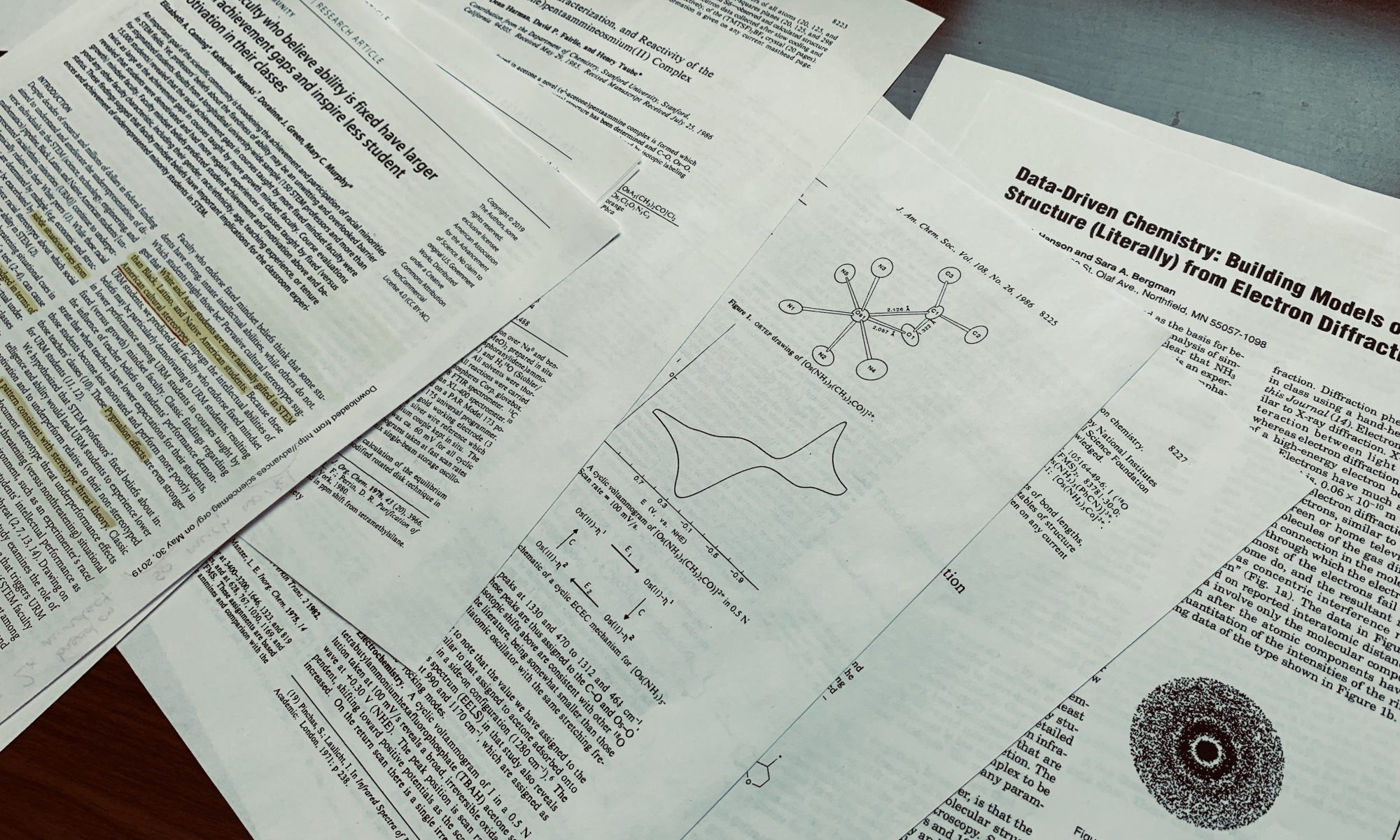 Scientific papers scattered about a table.