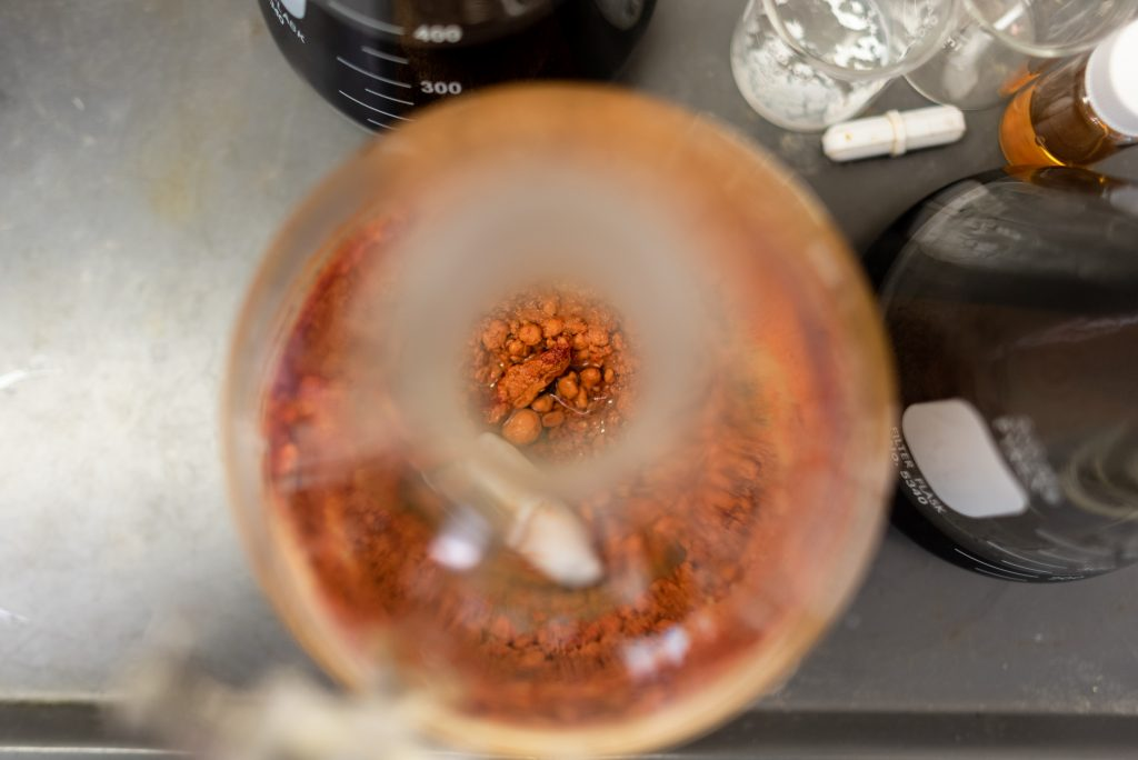 view down the opening of a round bottom flask with some orange solid inside