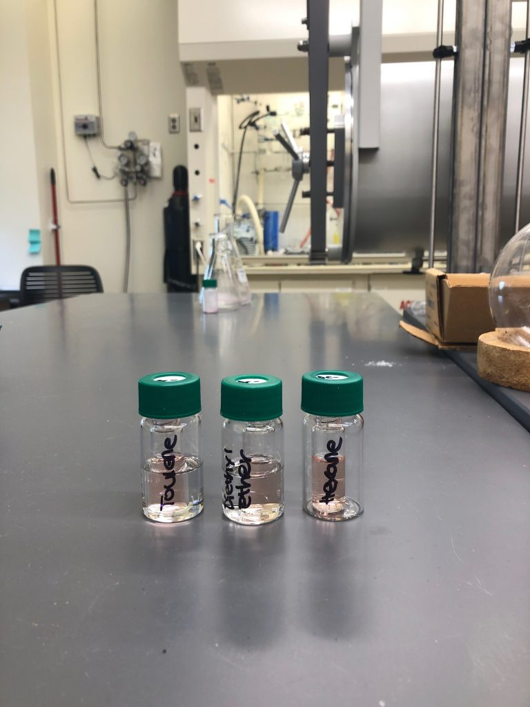 Three glass vials sitting on a table, with recrystallizations occurring in each one.