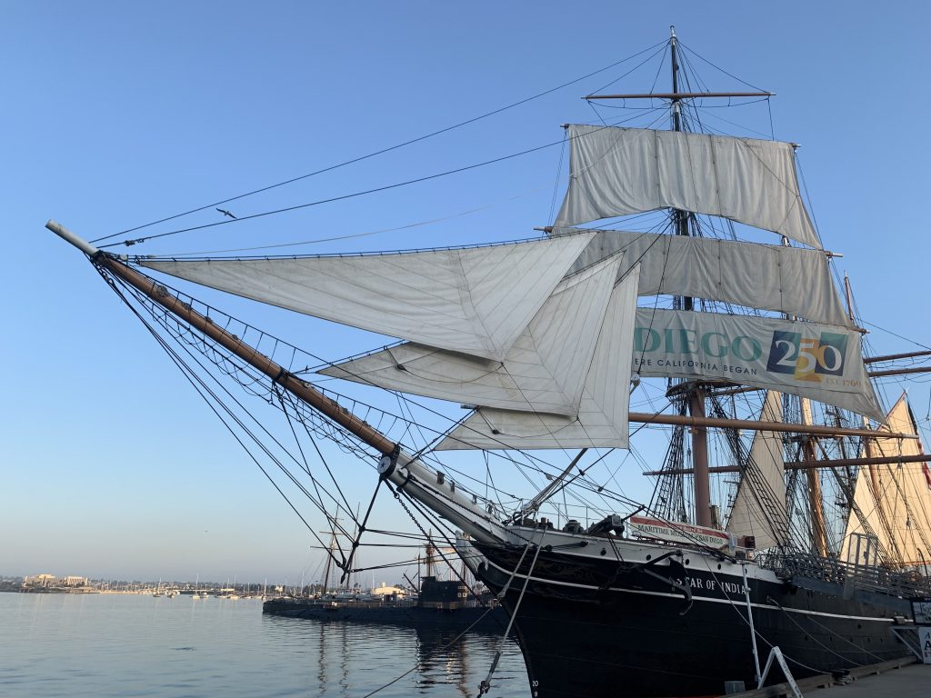A sailing ship from the 1800s with sails up at a dock
