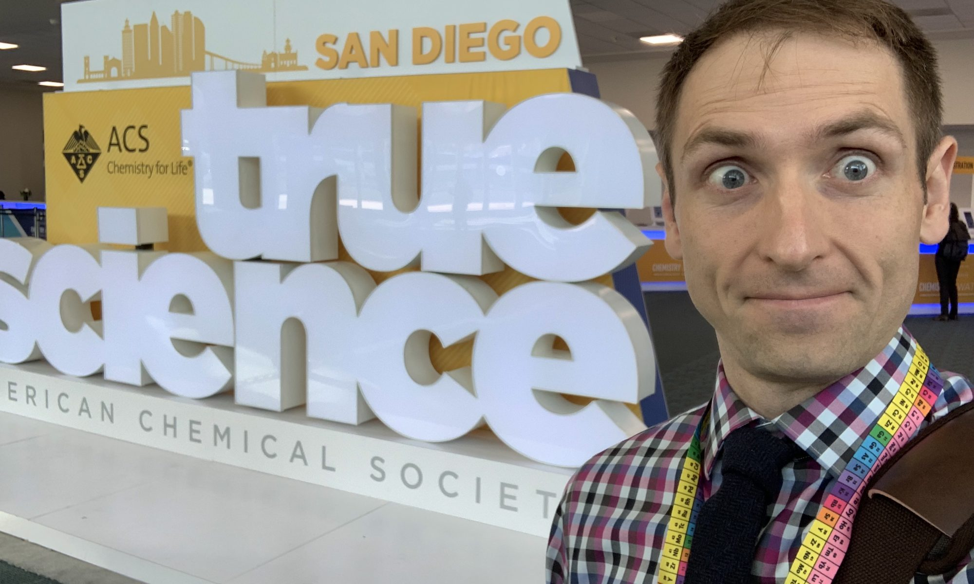 "Person standing next to a large sign that says ""True Science"""