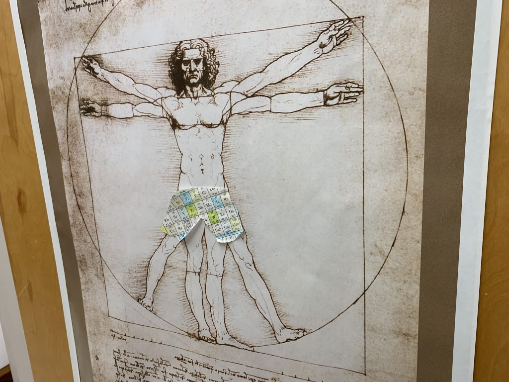 picture of a poster of Vitruvian Man but with a piece of the periodic table taped over his private parts