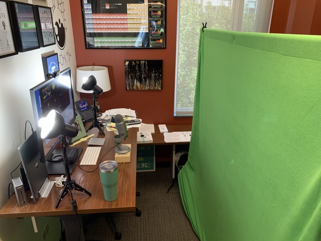"A picture of my office with a green piece of fabric suspended on a bar behind me, creating a background for the camera that was filming me at my computer. there are also two lights on my desk shining light that replicates the spectrum of sunlight to make my appearance more ""natural."""